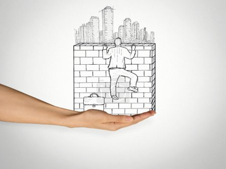 businessman climbing to the top of brick wall