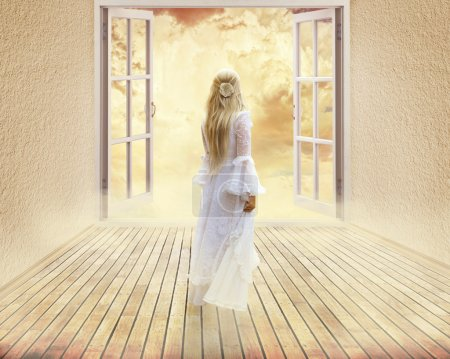 Photo pour Beautiful girl in white dress standing looking into open window dreamland day light surreal sky skyline view. Positive human emotion feeling happiness life perception success peace of mind concept - image libre de droit