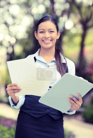Happy young businesswoman standing reading, company documents