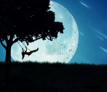 Photo for Silhouette of happy young woman on a swing of a tree isolated on beautiful background of moon, earth, night skyline, falling stars. Body vitality, human spirit wellbeing, freedom, happiness concept - Royalty Free Image