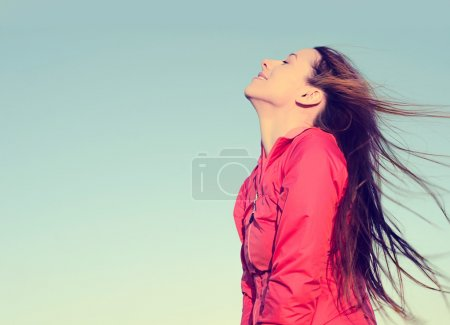 Woman smiling looking up to blue sky taking deep breath celebrating freedom.