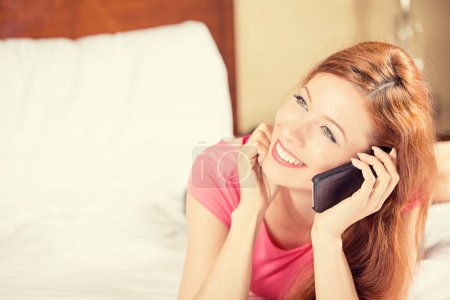 happy woman using mobile phone lying in bed