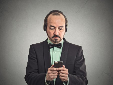Photo pour Portrait man listening to music with pair of headphones. Focused businessman in suit reading news on smart phone, holding mobile isolated grey wall background. Face expression of corporate executive - image libre de droit