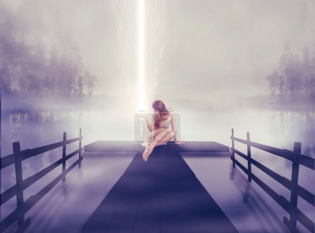 Foto de Lonely young woman sitting on a lake pier with bright ball of glowing light in her hand. Human emotion life perception feeling signs symbols, spirituality concept. Abstract idea screensaver background - Imagen libre de derechos