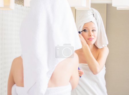 woman in hotel bathroom smiling after bath refreshing herself applying makeup