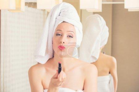 woman in hotel bathroom smiling after bath refreshing herself applying makeup