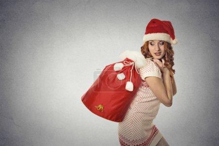 santa helper girl carrying big red christmas sack full of gifts