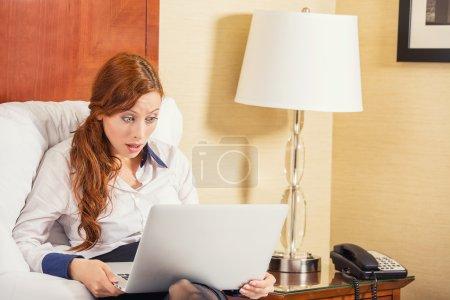 Photo pour Choqué jeune femme d'affaires à l'aide d'un ordinateur portable en regardant l'écran d'ordinateur soufflé dans la stupeur assis dans le lit à la maison, hôtel. Expression du visage humain, émotion, sentiment, perception, langage corporel, réaction - image libre de droit