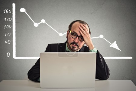 stressed man sitting at table with financial chart going down