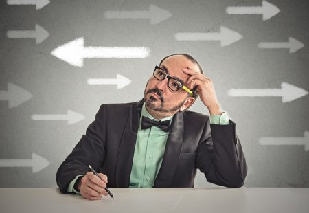 Photo for Uncertain guy looking at arrows. Man full of doubts hesitation. Closeup portrait puzzled business man thinking deciding something confused unsure isolated grey wall background. Emotion face expression - Royalty Free Image