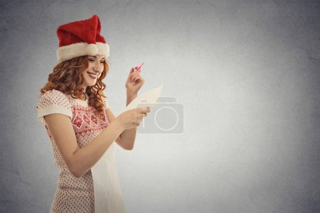 young attractive girl santa helper in red hat holding reading christmas wish list