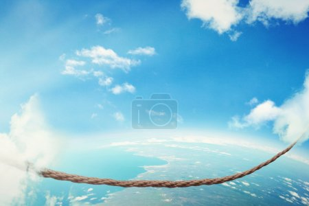 Photo for Managing risk big business challenges uncertainty concept. Walking on dangerous rope high in sky symbol of balance overcoming fear for goal success. Young entrepreneur in corporate world balancing act - Royalty Free Image