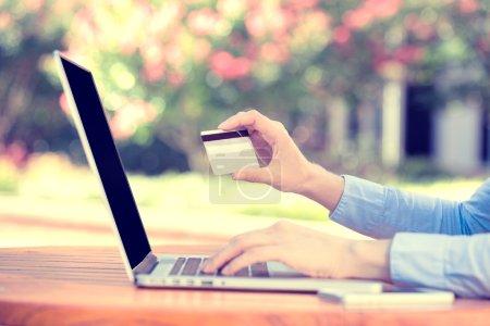 Photo pour Gros plan les mains de la jeune femme tenant une carte de crédit et utilisant un ordinateur portable pour faire des achats en ligne ou signaler une carte perdue, une transaction frauduleuse, une ville isolée en dehors de l'arrière-plan. Technologie de nouvelle génération - image libre de droit