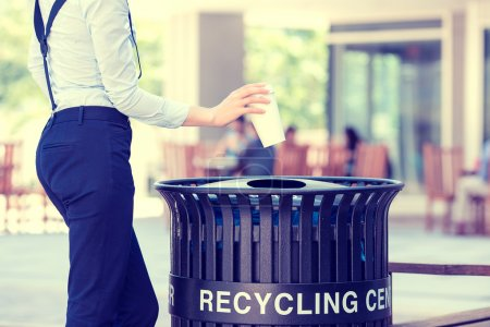 woman's hand throwing empty paper coffee cup in recycling bin