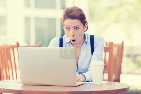 Photo pour Shocked young business woman using laptop looking at computer screen blown away in stupor sitting outside corporate office. Human face expression, emotion, feeling, perception, body language, reaction - image libre de droit