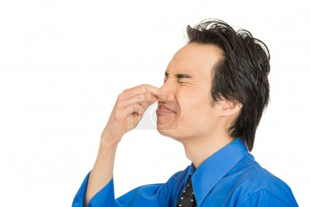 Man disgust on his face pinches his nose, something stinks bad smell