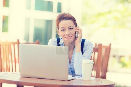 glückliche Frau, die auf dem Handy am Computer-Laptop arbeitet