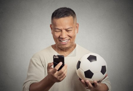 Smiling surprised man looking on smartphone watching game holding football