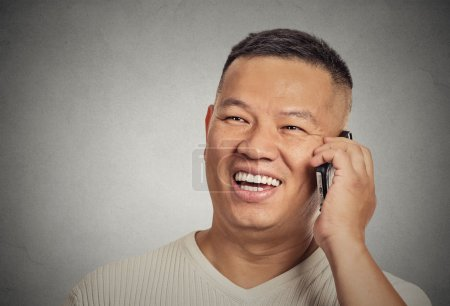 Photo pour Closeup portrait headshot handsome young man student happy guy excited employee, using cell phone, smiling, having pleasant conversation isolated grey wall background. Human emotion face expression - image libre de droit