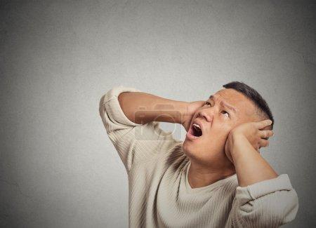 Photo pour Gros plan portrait fou furieux malheureux stressé homme couvrant ses oreilles levant les yeux, arrêter de faire du bruit fort il me donne mal de tête isolé fond de mur gris. Émotion humaine négative, expression du visage - image libre de droit