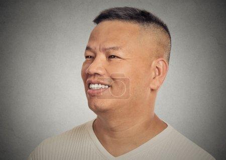 Foto de Closeup side profile headshot portrait happy smiling middle aged man isolated on grey wall background. Positive human face expression, emotion, feelings, life perception - Imagen libre de derechos