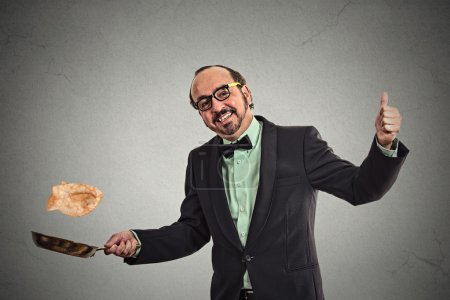 Photo for Happy smiling man tossing pancakes on frying pan isolated on grey wall background. Positive face expression emotion, Kitchen fun concept - Royalty Free Image