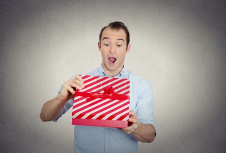 happy super excited surprised young man about to open unwrap red gift box