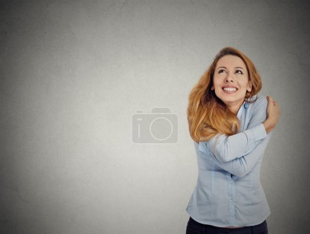confident woman holding hugging herself looking up