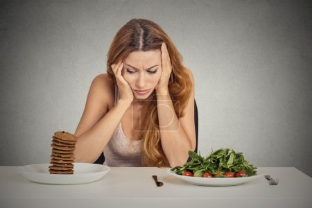 woman tired of diet restrictions deciding to eat healthy food or sweet cookies