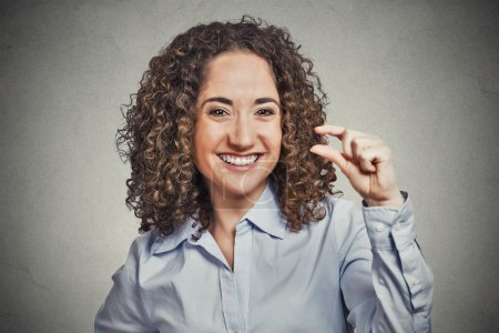 Foto de Closeup portrait, funny young curly brown hair woman showing small amount gesture with hand fingers isolated grey background. Human emotion facial expression feelings, body language, signs, symbols - Imagen libre de derechos