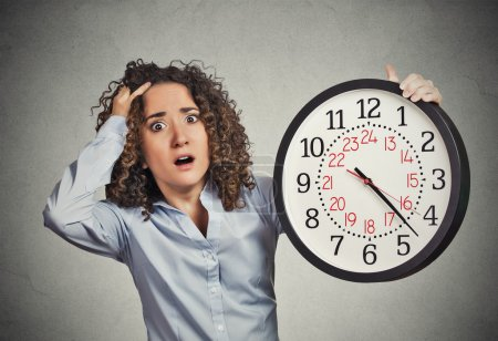 Photo for Time pressure. Closeup portrait woman stressed corporate employee holding clock looking anxiously running out of time isolated grey wall background. Human face expression emotion reaction. Last moment - Royalty Free Image