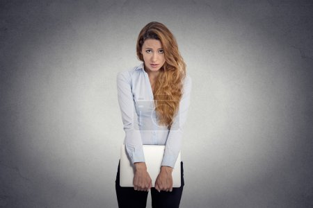 Photo for Lack of confidence. Insecure worried young woman holding laptop feels awkward isolated grey wall background. Human face expression emotion body language life perception - Royalty Free Image