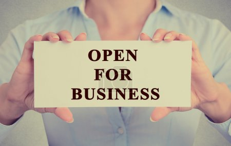 businesswoman hands holding white sign with message open for business