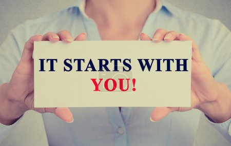 businesswoman hands holding white card sign with it starts with you!