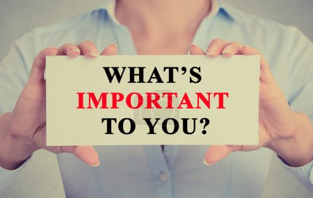 Businesswoman hands holding sign with What is important to you ? question