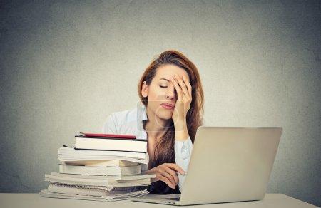 Photo pour Trop de travail fatigué somnolent jeune femme assise à son bureau avec des livres devant ordinateur portable isolé fond de bureau mur gris. Horaire chargé au collège, lieu de travail, concept de privation de sommeil - image libre de droit