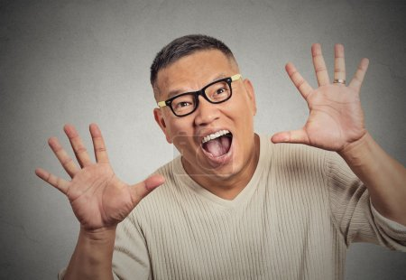 Super excited funky guy with glasses looking at you arms raised at camera