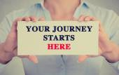 businesswoman hands holding card sign with Your Journey Starts Here message
