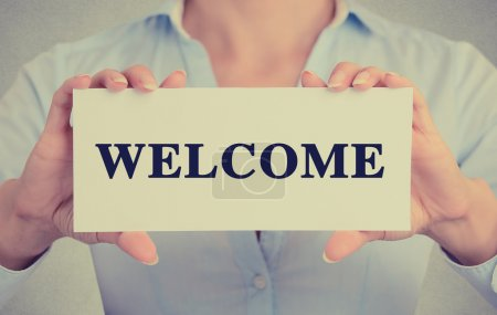 Photo pour Closeup businesswoman hands holding white card sign with welcome text message isolated on grey wall office background. Retro instagram style image - image libre de droit