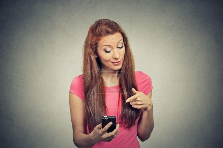angry woman unhappy, annoyed by something on her cell phone texting