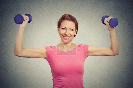 Fit healthy model woman flexing muscles lifting dumbbells