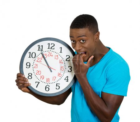 man holding wall clock, stressed biting fingernails pressured by lack of time