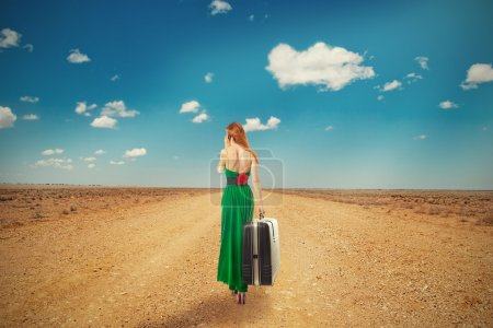 Photo for Beautiful woman walking through a desert road talking on mobile phone carrying big suitcase isolated on blue cloudy sky background. Embrace challenge unknown new life loneliness concept. Long journey - Royalty Free Image