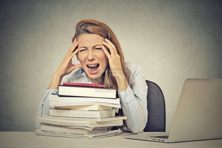 stressed screaming woman sitting at desk with books computer
