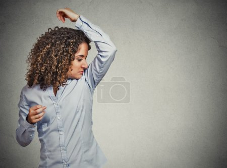 woman smelling sniffing her armpit something stinks