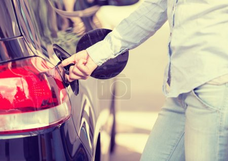 Woman opening car gas tank cap at petrol station