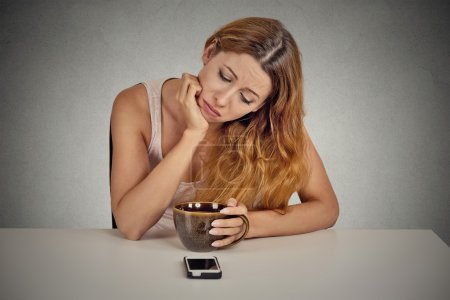Photo pour Sad depressed young woman sitting at table drinking coffee looking at her mobile phone waiting for a call text message isolated on grey wall background. - image libre de droit
