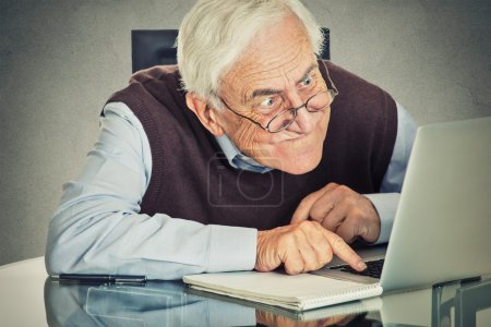 Photo for Elderly old man using computer sitting at table isolated on grey wall background. Senior people and technology concept - Royalty Free Image