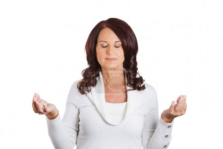Woman with eyes closed hands raised in air meditat...