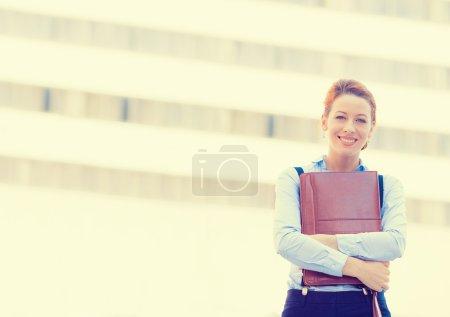 Photo pour Portrait de confiant souriant heureuse jolie jeune femme professionnelle debout sur un fond de bureau de la ville d'entreprise. Expression faciale positive - image libre de droit